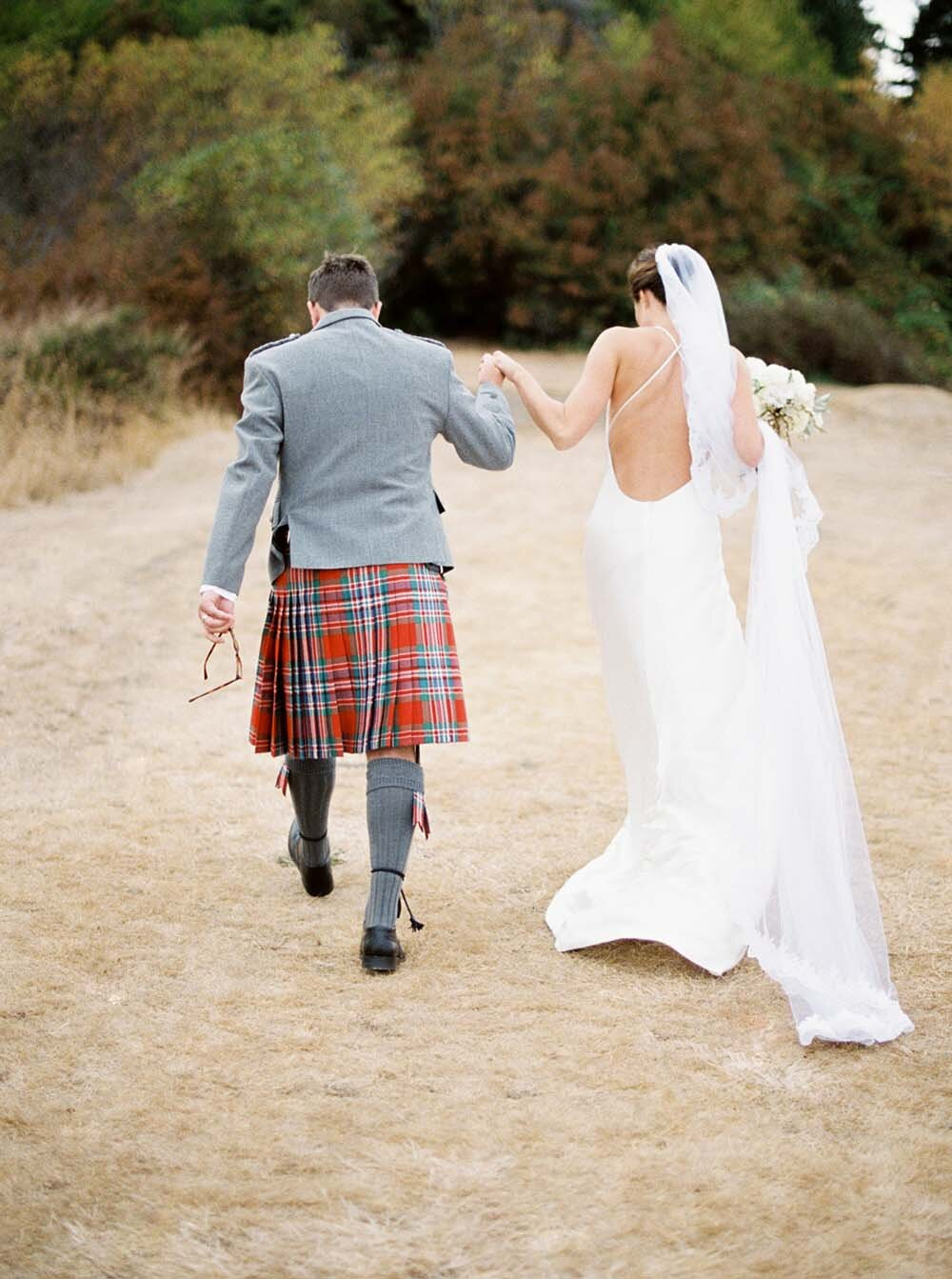 bride and groom facing away from the camera, walking away during the recessional, bride holding bouquet and groom in a kilt, holding hands with each other